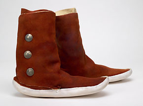 These boots in the traditional Navajo-style were made by Martin Lovato, a Santo Domingo Pueblo. Men did the work of tanning and making footwear and other hide goods in Pueblo communities.Brain tanned deerskin upper, commercial cowhide sole, silver, sinew, Gismark pigmentSanta Domingo Pueblo, 1981S81.365