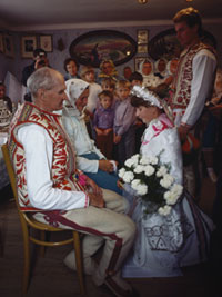 A bride in a traditional wedding costume from the region of Lendak, Slovak, kneels before her parents to bid farewell at her wedding, while her groom looks on.