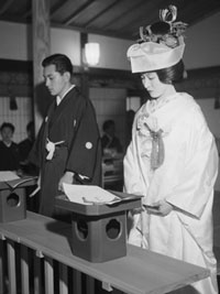 A young Japanese couple perform the traditional marriage ceremony in a temple.