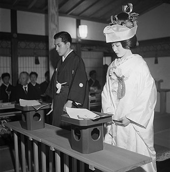 A young Japanese couple perform the traditional marriage ceremony in a temple